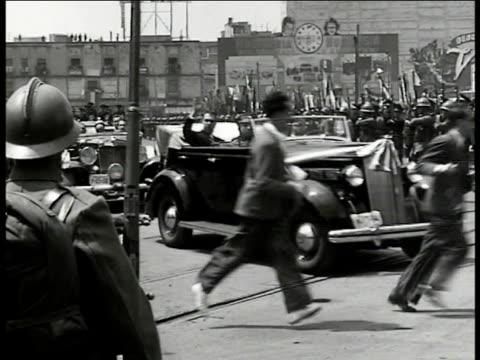 vídeos y material grabado en eventos de stock de mexico president lazaro cardenas in convertible car driving through street waving to soldiers lined up ws police holding crowd back ws rich... - 1970