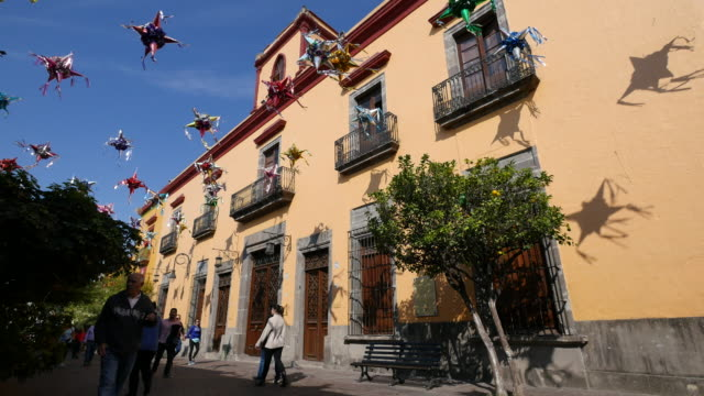 mexico tlaquepaque pinata shadows on a yellow building - papier stock videos & royalty-free footage
