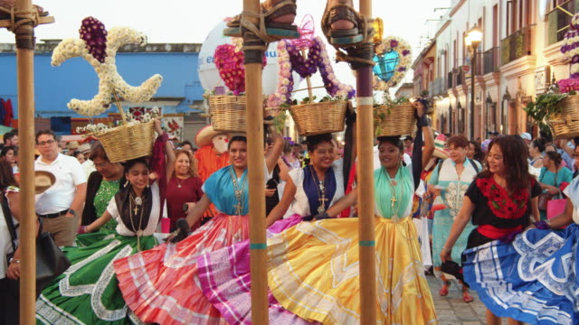 mexico tradition. calendas is a parade and celebration typical from oaxaca. mexican women named chinas dressed in traditional costume. they are dancing performing a choreography with the colorful skirts. walking stilts in the foreground - cultures stock videos & royalty-free footage