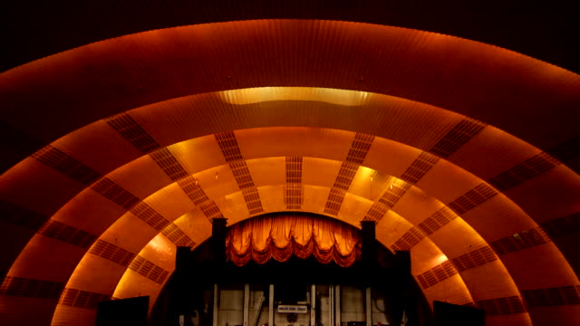 td ceiling to overlooking empty auditorium rows of seats aisles stage raised curtain proscenium arch w/ attached speakers monitors - radio city music hall stock videos & royalty-free footage