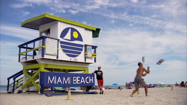 miami beach lifeguard station and a man throwing an american football in front of it, miami, florida - miami beach stock videos & royalty-free footage