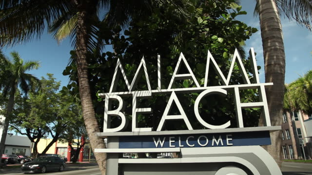 Miami Beach Welcome sign w/ vehicles driving up down city street on either side palm trees