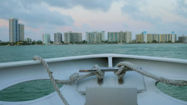 Miami city skyline at sunset or dusk. Boat tour in the Biscayne Bay. Point of view image with a 50mm lens. Florida, United States