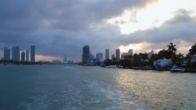 miami city skyline during sunset or dusk, point of view from the sea while traveling in boat tour - miami dade county stock videos and b-roll footage