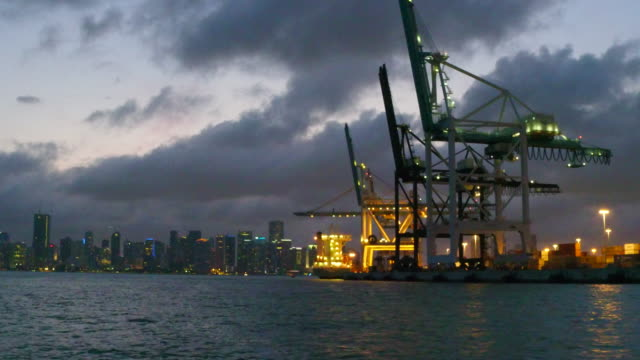 miami, united states: port cranes and metallic structure at night. point of view from the biscayne bay. the tourist boat tour of the city is a major tourist attraction in the american human settlement - boat point of view stock videos and b-roll footage