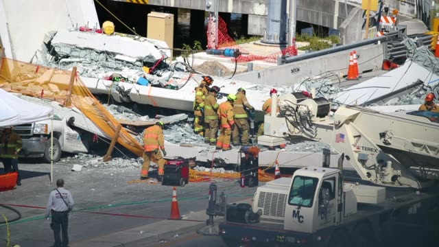 miamidade fire rescue department personel and other rescue units work at the scene where a pedestrian bridge collapsed a few days after it was built... - bridge built structure stock videos and b-roll footage