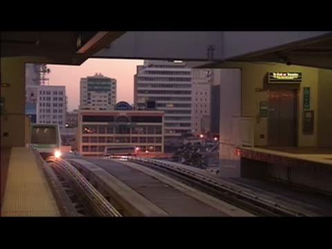 vídeos de stock e filmes b-roll de miami-dade transit metromover train pulling into station at twilight / doors sliding open / miami, florida - formato letterbox