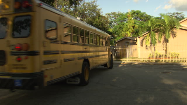ms miamidade yellow school bus driving around corner up neighborhood street small house palm trees on right - miami dade school stock videos and b-roll footage