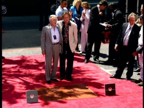 michael and kirk douglas pose for photos in front of michael's handprints and footprints. - kirk douglas actor stock videos & royalty-free footage