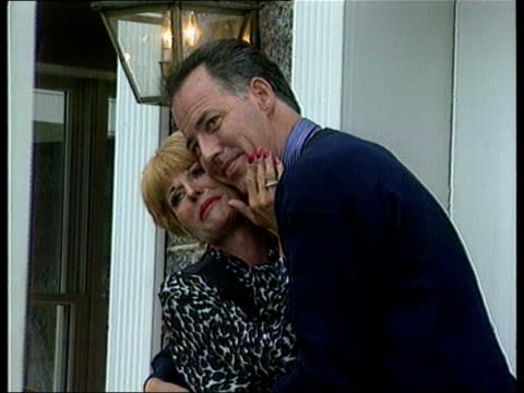 michael barrymore - autobiography postponed/ perjury investigation; unknown location: barrymore and then wife cheryl embrace unknown location:... - michael barrymore stock-videos und b-roll-filmmaterial