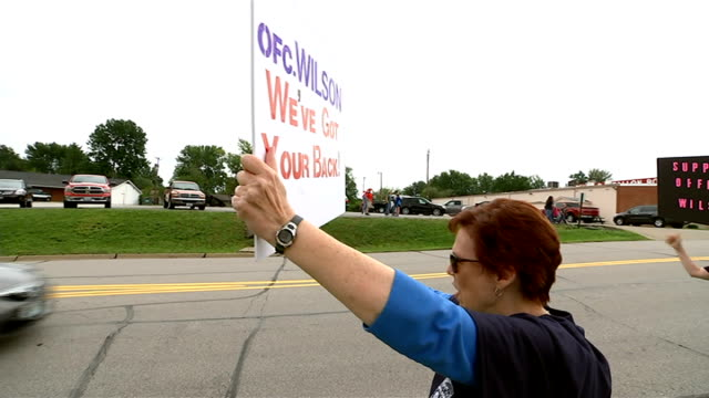 One month on DAY Back view woman holding up sign 'Ofc Wilson We've Got Your Back' and cheering as car drives past and sounds horn SOT Wide shot...