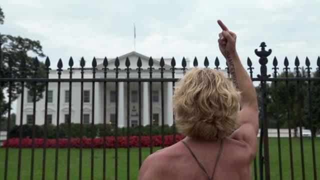 vidéos et rushes de michael brown protester with text on bare chest flipping off the white house - un seul homme d'âge moyen