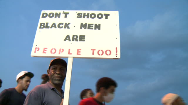 stockvideo's en b-roll-footage met ktvi michael brown protesters walk past police with bulletproof vests and plastic handcuffs on august 18 2014 in ferguson missouri protests and riots... - black lives matter