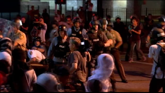 attorney general meets local leaders usa missouri ferguson police officer pointing assault rifle at crowd of protesters and journalists and telling... - ミズーリ州点の映像素材/bロール