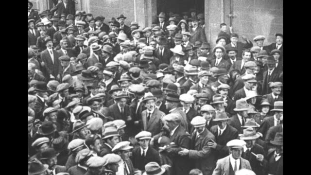 vídeos y material grabado en eventos de stock de michael collins is enveloped in a large crowd / he rides in an open car escorted by irish volunteers / collins stands on platform, delivering speech... - irlanda del norte