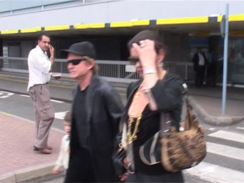 michael douglas and catherine zeta jones arrive at heathrow with chiidren dylan and carys. female staff member pushes luggage trolley as they walk... - キャサリン・ゼタ・ジョーンズ点の映像素材/bロール