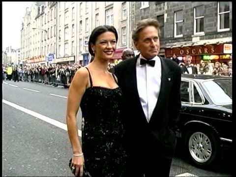 michael douglas and catherine zeta jones go to court over pictures; scotland: edinburgh: zeta jones and husband douglas arriving at film premiere - キャサリン・ゼタ・ジョーンズ点の映像素材/bロール