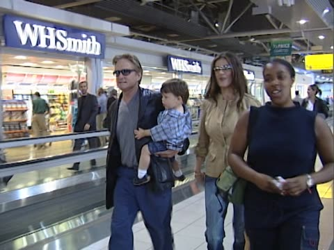 michael douglas and catherine zeta jones stride rapidly through heathrow to board a flight. douglas carries toddler dylan and camera operator... - striding stock videos & royalty-free footage