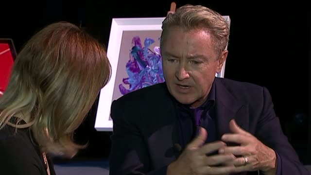 vídeos de stock e filmes b-roll de michael flatley interview on his paintings michael flatley interview with reporter in shot sot on how he started painting / using his feet to paint /... - wembley arena