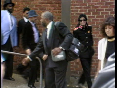 michael jackson arrives at heathrow; itn england: lap: ext pop star michael jackson along down ramp accompanied by bodyguards l-r pull out as towards... - マイケル・ジャクソン点の映像素材/bロール