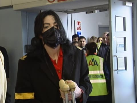 michael jackson gets off flight at heathrow from us on crutches after breaking his foot in earlier incident. greets two friends who were on the same... - マイケル・ジャクソン点の映像素材/bロール