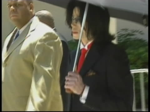 michael jackson holds an umbrella as he walks and waves. - courthouse stock videos & royalty-free footage
