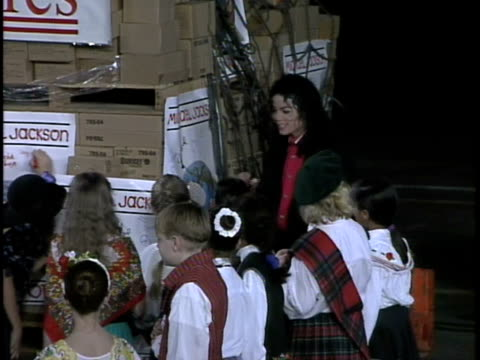 Michael Jackson in hangar w/ children from choir talking to children signing poster on boxes