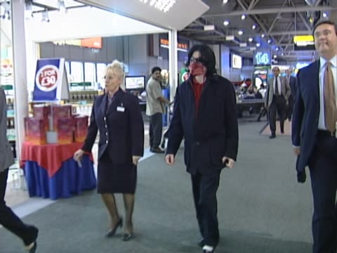 vídeos y material grabado en eventos de stock de michael jackson rushes through heathrow to catch a flight to the usa. an aide carries a box of toys beside him and he removes his sun glasses and... - autografiar