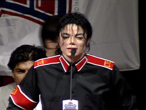 michael jackson standing on stage speaking about heal the world foundation helping underprivileged children thanking various supporters - super bowl stock videos & royalty-free footage