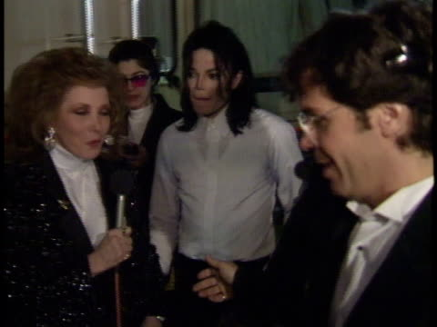 vídeos y material grabado en eventos de stock de michael jackson walking through parking lot w/ security female reporter jeannie asking question jackson nodding saying yes security saying no... - 1993