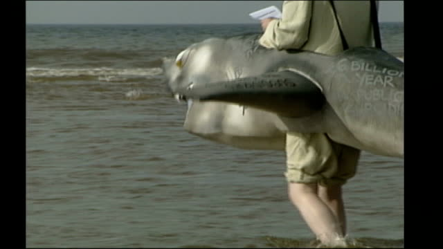 michael meacher launches labour leadership bid tx blackpool ext man wearing shark costume meacher swimming in sea side view shark face zoom in... - swimming costume stock videos & royalty-free footage