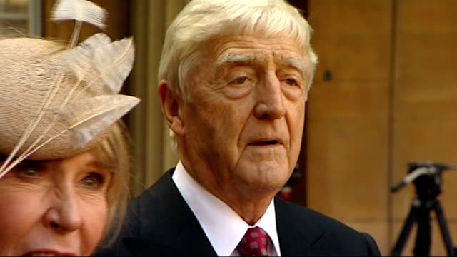 stockvideo's en b-roll-footage met michael parkinson receives knighthood press arranging photocall with parkinsons / mary parkinson placing medal around michael parkinson's neck /... - michael parkinson