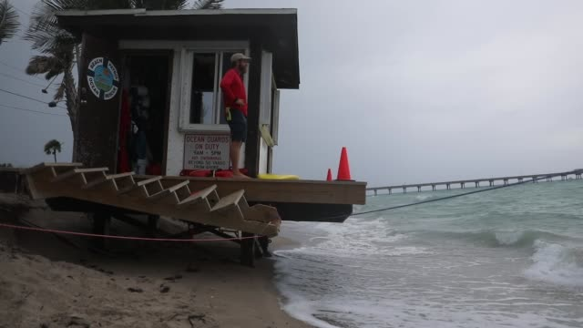 vídeos de stock, filmes e b-roll de michael vasta a dania beach lifeguard stands on his lifeguard stand that is in danger of being swept out to sea on june 8 2018 in dania beach florida... - erodido