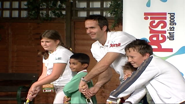 london int general view of michael vaughan posing for photocall playing cricket with children / onlookers / more of vaughan photocall with children... - pink shirt stock videos and b-roll footage