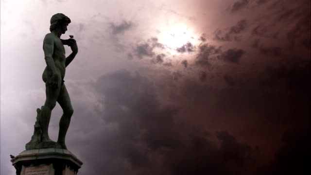 Michaelangelo's statue of David stands against a burnished sky. Available in HD.