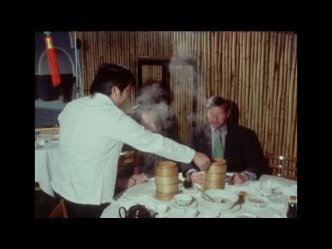 michelin restaurant guide:; a) pre comm england: london: soho: int chinese waiters serve sandy ekt 16mm itn 18 secs 11 ft 21.3.74 / nat - restaurant stock videos & royalty-free footage