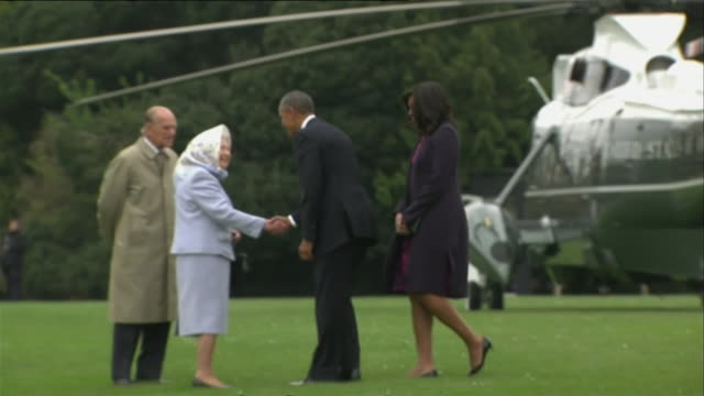 michelle and barack obama are greeted by the queen and the duke of edinburgh before they get into a car which was driven by the duke of edinburgh,... - königshaus stock-videos und b-roll-filmmaterial