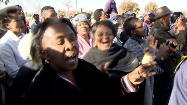 michelle obama urges young people to fight stigma of hiv/aids; south africa: soweto: ext crowd singing and dancing in lead up to arrival of michelle... - retrovirus video stock e b–roll