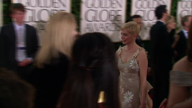 michelle williams and busy phillips hold hands as they walk down the red carpet at beverly hilton hotel - michelle williams actress stock videos and b-roll footage