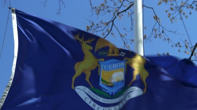 vídeos de stock e filmes b-roll de michigan state flag waving in the breeze - michigan