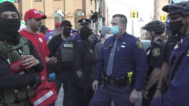 michigan state police create a barrier of trump supporters and counterprotestors nearby the michigan state capitol building after democratic... - michigan stock-videos und b-roll-filmmaterial