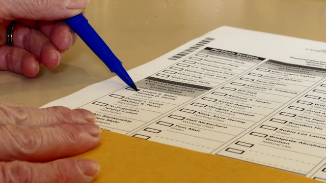 michigan voter signs her mail-in presidential ballot on her kitchen table. due to the covid-19 pandemic, millions of mail-in ballots will be used by... - wahlschein stock-videos und b-roll-filmmaterial