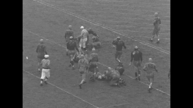 Michigan Wolverines' Tom Harmon punts ball out of bounds to Minnesota Golden Gophers / Gophers' Bill Daly fumbles and Wolverines recover / Harmon...