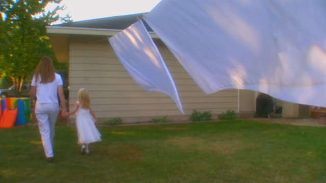 michiganmother walking with daughter along side a house - washing line stock videos and b-roll footage