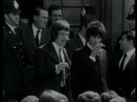vídeos y material grabado en eventos de stock de official papers released on sixties drugs raid 47752/398 1051967 london footage jagger and keith richard stand on steps outside court with police in... - 1960 1969