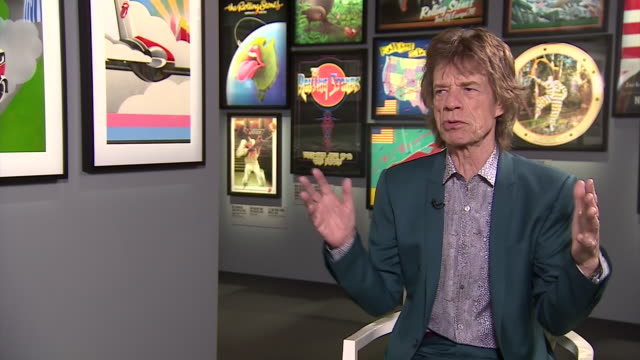 mick jagger talking about how the longevity of the rolling stones has made them more than just a rock band at an exhibition featuring the band - ausstellung stock-videos und b-roll-filmmaterial
