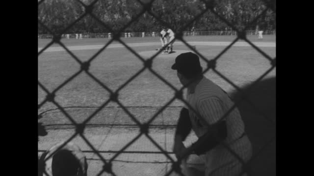 mickey mantle bats as the new york yankees conduct spring training in fl / team runs out on field, followed by manager casey stengel / #8 yogi berra... - ニューヨーク・ヤンキース点の映像素材/bロール