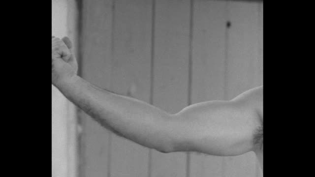 VS Mickey Walker expands his shirtless chest flexes his arms shows his fist as voice over describes his measurements / MS Walker works speed bag hits...
