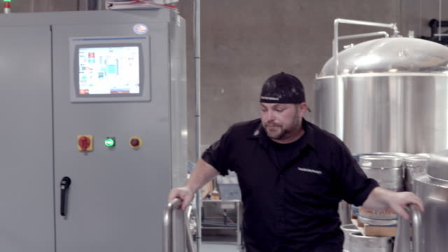 WS micro brewery brew master climbs stairs of elevated platform and approaches computer control panel  / Thousand Palms, California, USA