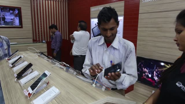 Micromax signage is displayed outside the company's Micromax World store in New Delhi India on Tuesday March 17 An employee attends to a customer...